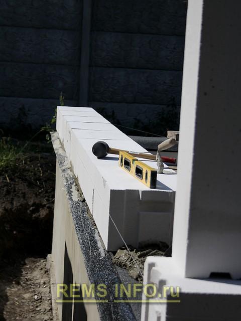 Корректировка ровности кладки стен из газоблока с помощью уровня.