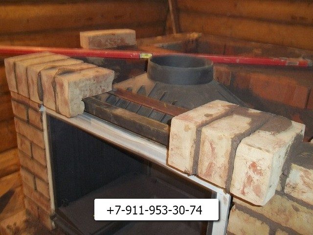 Процесс укладки кирпича на верхнюю часть каминной камеры.